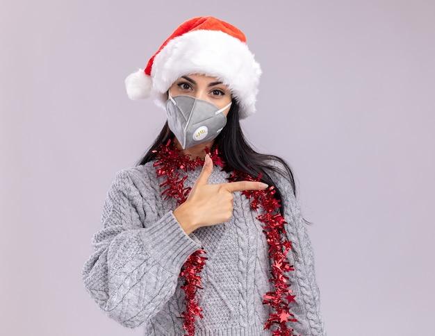 Уверенная молодая кавказская девушка в новогодней шапке и гирлянде из мишуры на шее с защитной маской смотрит в камеру, указывая на сторону, изолированную на белом фоне с копией пространства