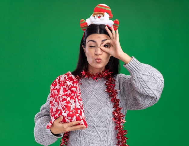 Confident young caucasian girl wearing santa claus headband and tinsel garland around neck holding christmas gift sack  doing look gesture pursing lips with one eye closed isolated on green wall