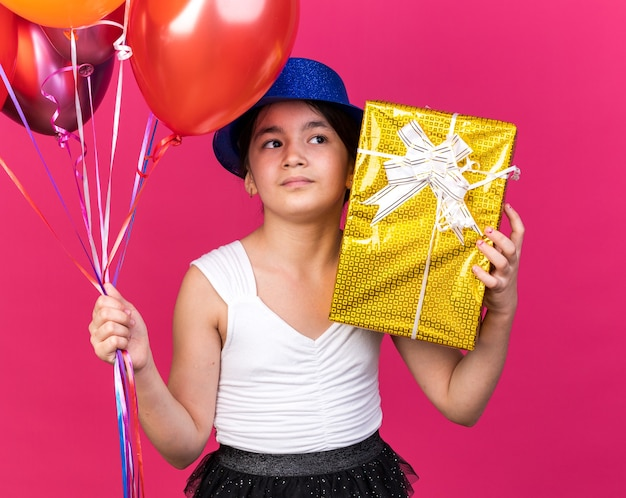 Confident young caucasian girl with blue party hat holding gift box and helium balloons looking at side isolated on pink wall with copy space