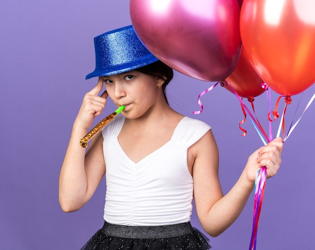 Confident young caucasian girl with blue party hat holding helium balloons and blowing party whistle isolated on purple wall with copy space