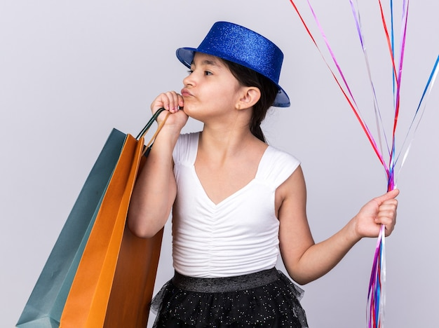 Confident young caucasian girl with blue party hat holding helium balloons and shopping bags looking at side isolated on white wall with copy space