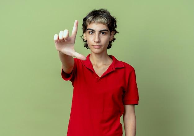 Уверенная молодая кавказская девушка со стрижкой пикси делает жест неудачника на камеру, изолированную на оливково-зеленом фоне с копией пространства
