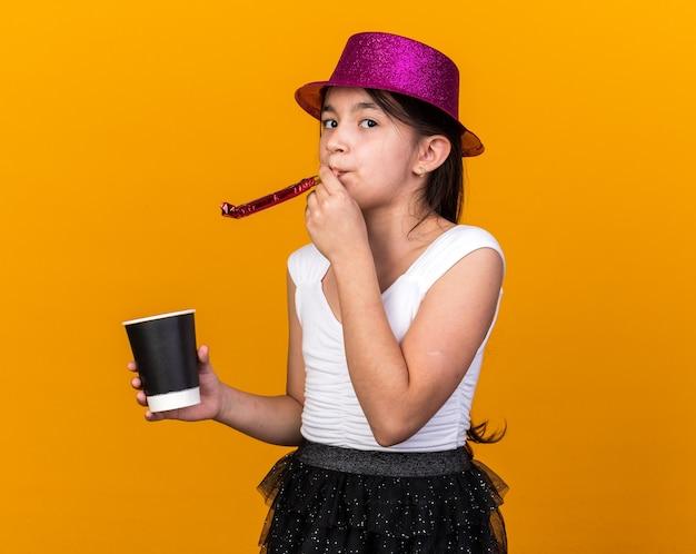Fiducioso giovane ragazza caucasica con viola party hat tenendo il bicchiere di carta e soffiando il fischio del partito isolato sulla parete arancione con spazio di copia