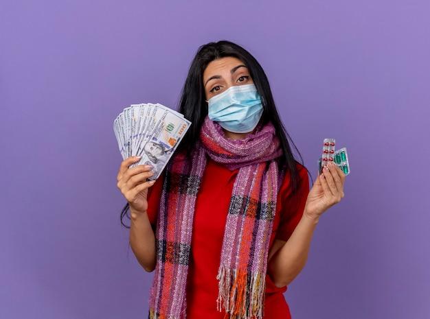 Fiduciosa giovane ragazza malata caucasica indossando maschera e sciarpa tenendo i soldi e confezioni di capsule isolate sulla parete viola con lo spazio della copia