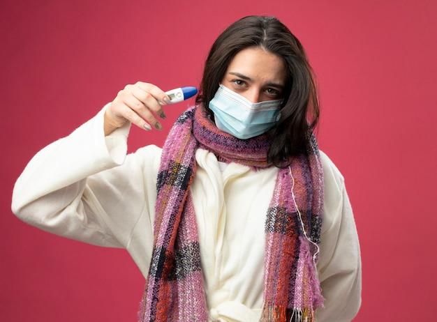 Уверенная молодая кавказская больная девушка в халате и шарфе с маской, держащая термометр, изолированную на малиновой стене