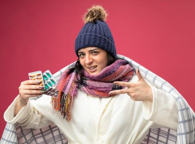 크림슨 벽에 고립 된 손으로 3을 보여주는 캡슐의 격자 무늬를 들고 팩에 싸여 가운 겨울 모자와 스카프를 착용 확신 젊은 백인 아픈 소녀