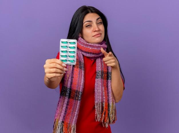 スカーフを身に着けている自信を持って若い白人の病気の女の子は、コピースペースで紫色の壁に隔離されたカプセルのパックを探して指しています