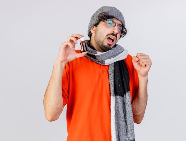 眼鏡をかけている自信を持って若い白人の病気の人冬の帽子とガラスの中に薬を保持しているスカーフは、コピースペースのある白い壁に隔離された強いジェスチャーをしています