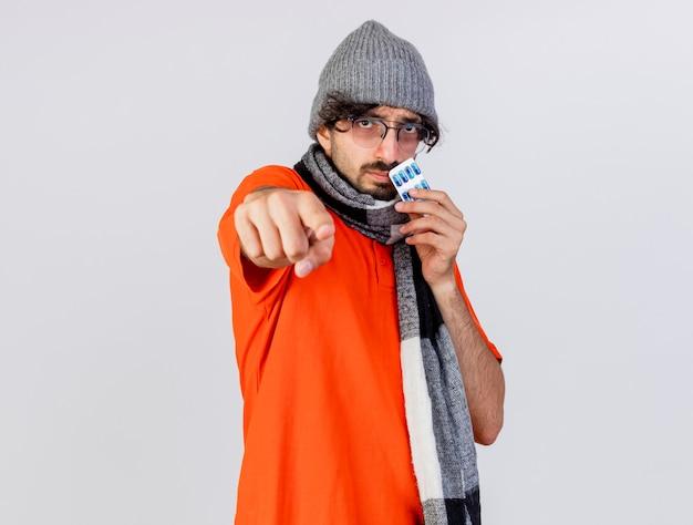 Fiducioso giovane uomo malato caucasico con gli occhiali cappello invernale e sciarpa che tiene il pacchetto di capsule mediche guardando e indicando la fotocamera isolata su sfondo bianco con spazio di copia