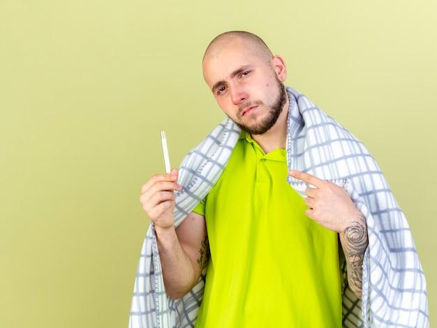 Fiducioso giovane uomo malato caucasico avvolto in prese di plaid e punti al termometro isolato sulla parete verde oliva con lo spazio della copia