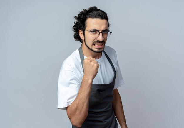 Уверенный молодой кавказский мужчина-парикмахер в очках и волнистой повязке для волос в униформе сжимает кулак, изолированные на белом фоне с копией пространства