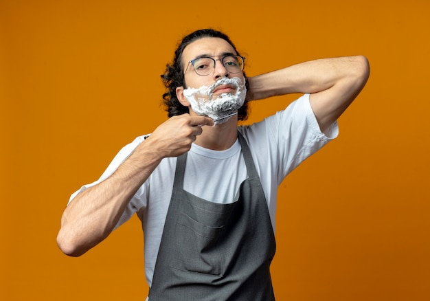 Уверенный молодой кавказский парикмахер в очках и с волнистой лентой для волос в униформе бреет собственную бороду опасной бритвой, кладя руку за голову с кремом для бритья, нанесенным на лицо