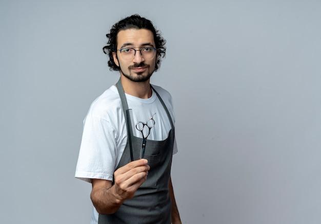Уверенный молодой кавказский мужчина-парикмахер в очках и волнистой повязке для волос в униформе, протягивая расческу и ножницы перед камерой, изолированной на белом фоне с копией пространства