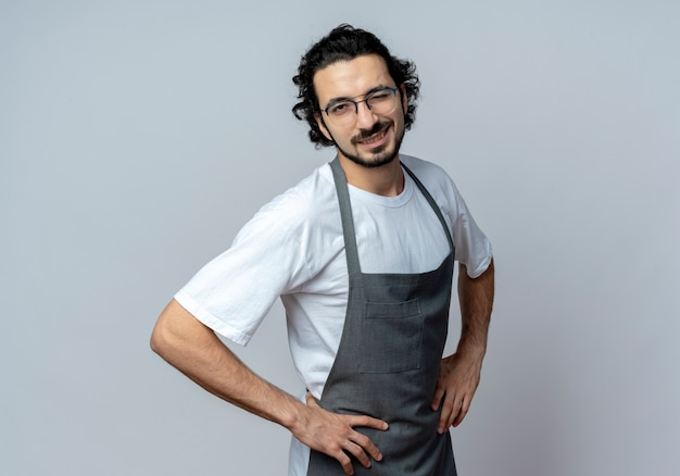 Уверенный молодой кавказский мужчина-парикмахер в очках и волнистой повязке для волос в униформе, подмигивая и кладя руки на талию, изолированные на белом фоне с копией пространства