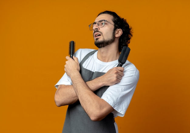 Confident young caucasian male barber wearing glasses and wavy hair band in uniform holding combs keeping hands crossed looking straight isolated on orange background with copy space