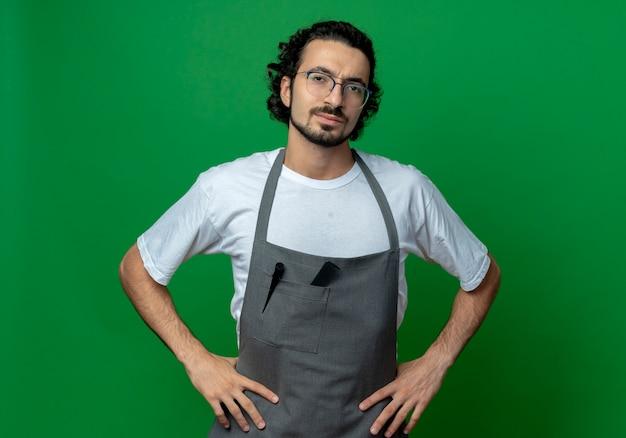 Fiducioso giovane maschio caucasico barbiere con gli occhiali e fascia per capelli ondulati in uniforme che mette le mani sulla vita isolato su priorità bassa verde