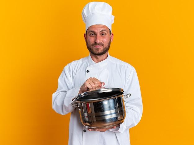Fiducioso giovane maschio caucasico cuoco in uniforme da chef e cappello che tiene la pentola afferrando il coperchio