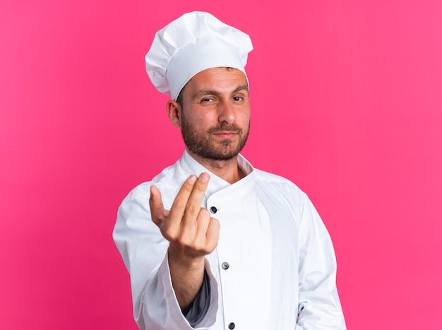 Fiducioso giovane maschio caucasico cuoco in uniforme da chef e berretto guardando la telecamera facendo venire qui gesto isolato sulla parete rosa