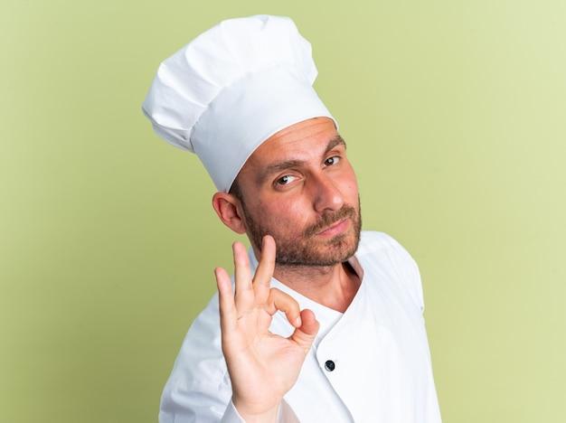 올리브 녹색 벽에 격리된 확인 표시를 하는 카메라를 보고 프로필 보기에 서 있는 모자와 요리사 유니폼을 입은 자신감 있는 젊은 백인 남성 요리사