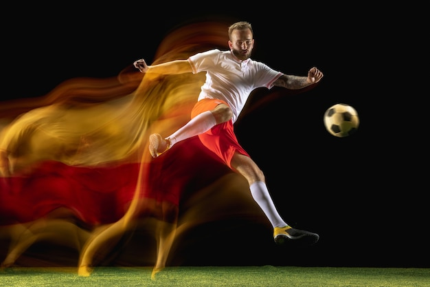 Confident. young caucasian male football or soccer player in sportwear and boots kicking ball for the goal in mixed light on dark wall. concept of healthy lifestyle, professional sport, hobby.