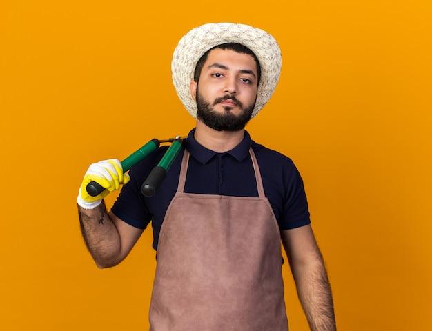 Уверенный в себе молодой кавказский садовник в садовой шляпе и перчатках, держащий садовые ножницы на плече, изолированный на оранжевой стене с копией пространства