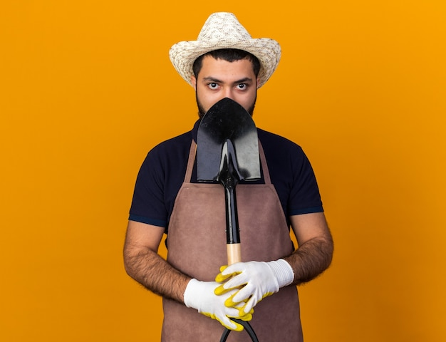 Fiducioso giovane maschio caucasico giardiniere che indossa cappello da giardinaggio e guanti tenendo la vanga isolata sulla parete arancione con spazio di copia