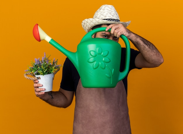 Confident young caucasian male gardener wearing gardening hat holding flowerpot and looking  through watering can isolated on orange wall with copy space