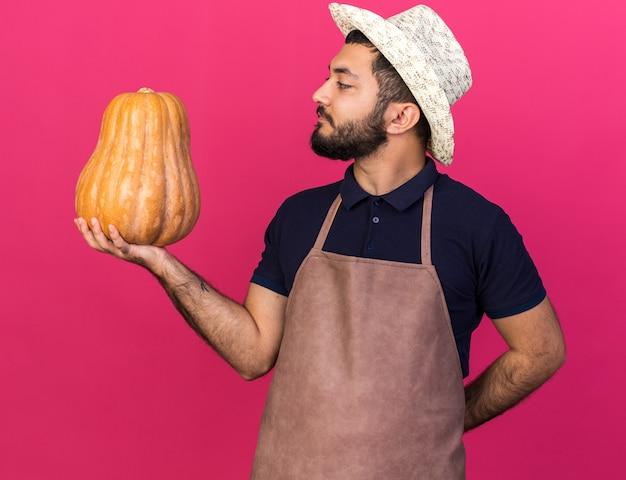 Fiducioso giovane giardiniere maschio caucasico indossando il cappello da giardinaggio tenendo e guardando la zucca isolato sulla parete rosa con spazio di copia