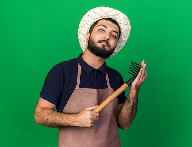 Fiducioso giovane maschio caucasico giardiniere che indossa cappello da giardinaggio tenendo rastrello e guardando isolato sulla parete verde con spazio di copia