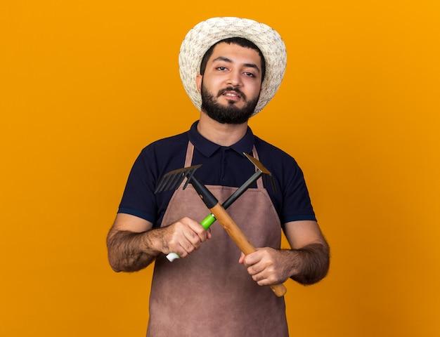 ガーデニング帽子をかぶっている自信を持って若い白人男性の庭師は、コピースペースでオレンジ色の壁に分離された交差する熊手とくわ熊手を保持します