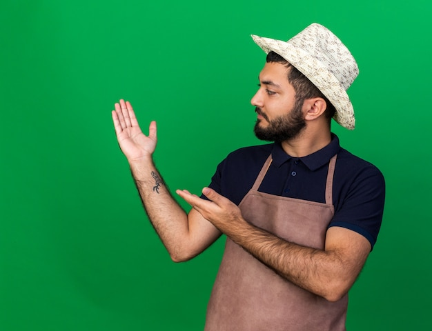 Fiducioso giovane maschio caucasico giardiniere che indossa cappello da giardinaggio guardando e indicando la sua mano vuota isolata sulla parete verde con spazio di copia