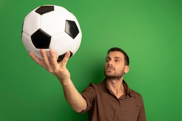 Уверенный молодой кавказский мужчина протягивает футбольный мяч к камере, глядя на нее на зеленом фоне