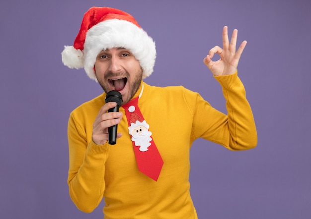 Confident young caucasian man wearing christmas hat and tie holding microphone singing looking at camera doing ok sign isolated on purple background