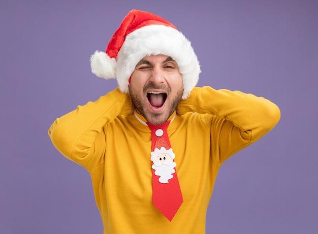 Fiducioso giovane uomo caucasico che indossa il cappello di natale e cravatta tenendo le mani dietro il collo guardando la telecamera sbattere le palpebre con la bocca aperta isolata su sfondo viola