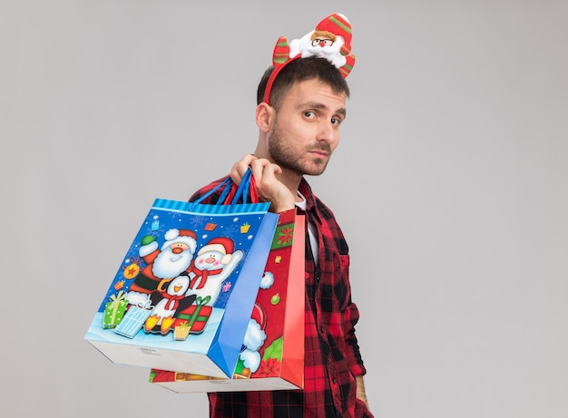 Fiducioso giovane uomo caucasico indossando la fascia di natale in piedi in vista di profilo tenendo i sacchetti di regalo di natale sulla spalla guardando la telecamera isolata su sfondo bianco con spazio di copia