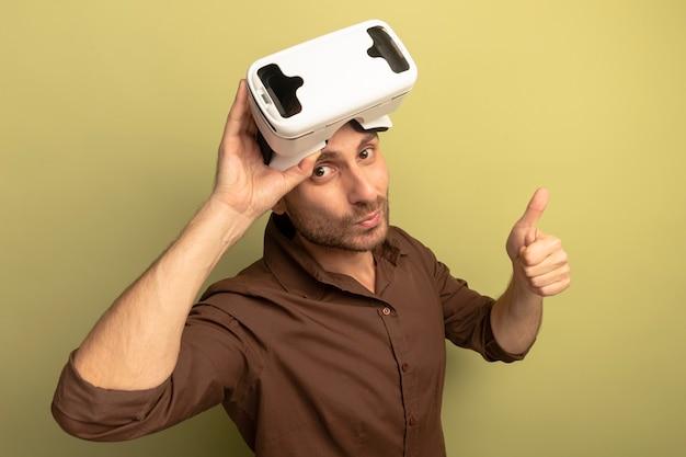 Уверенный молодой кавказский мужчина в гарнитуре vr на голове, хватая ее, показывая большой палец вверх, глядя в камеру, изолированную на оливково-зеленом фоне