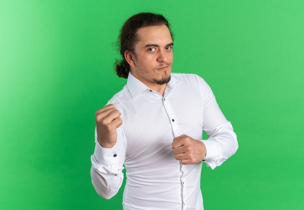 Confident young caucasian man in white shirt keeping fists ready to punch isolated on green wall with copy space