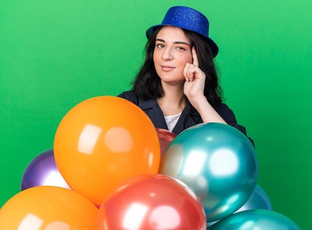 緑の壁に隔離された思考ジェスチャーをしている正面を見て風船の後ろに立っているパーティーハットを身に着けている自信を持って若い白人のパーティーの女性