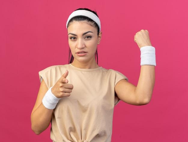 머리띠와 팔찌를 착용하고 분홍색 벽에 격리된 주먹을 꽉 쥐고 가리키는 자신감 있는 젊은 백인 스포티 소녀