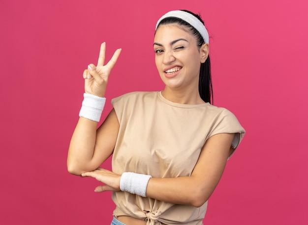 머리띠와 팔찌를 착용한 자신감 있는 젊은 백인 스포티 소녀는 분홍색 벽에 격리된 평화 사인을 하며 앞을 바라보며 윙크를 합니다.