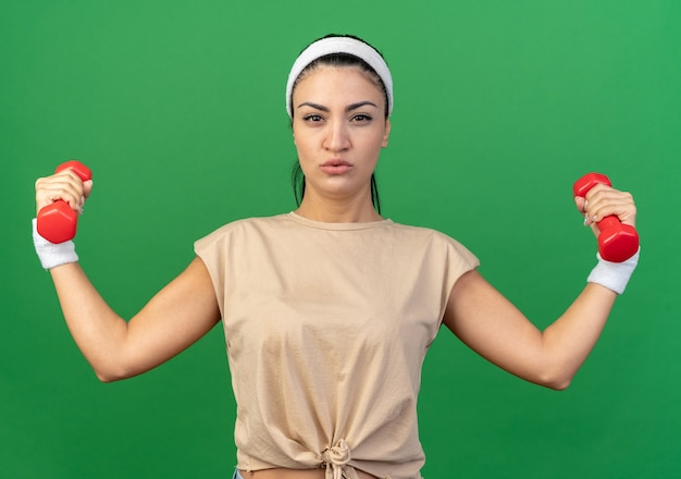 머리띠와 팔찌를 끼고 녹색 벽에 격리된 앞을 바라보는 아령을 들고 있는 자신감 있는 젊은 백인 스포티 소녀
