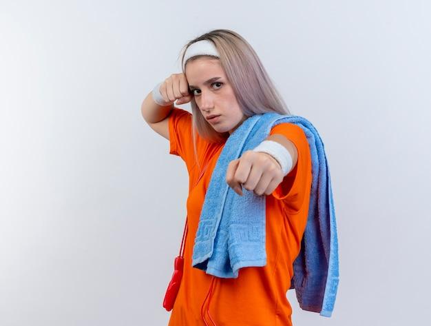 중괄호와 머리띠와 어깨에 수건을 들고 팔찌를 착용하는 목 주위에 밧줄 점프 자신감이 젊은 백인 스포티 한 소녀는 주먹을 흰 벽에 펀치 준비를 유지합니다