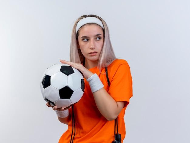 Уверенная молодая кавказская спортивная девушка с подтяжками и прыжками со скакалкой на шее в головной повязке и браслетах держит мяч, глядя в сторону, изолированную на белой стене с копией пространства