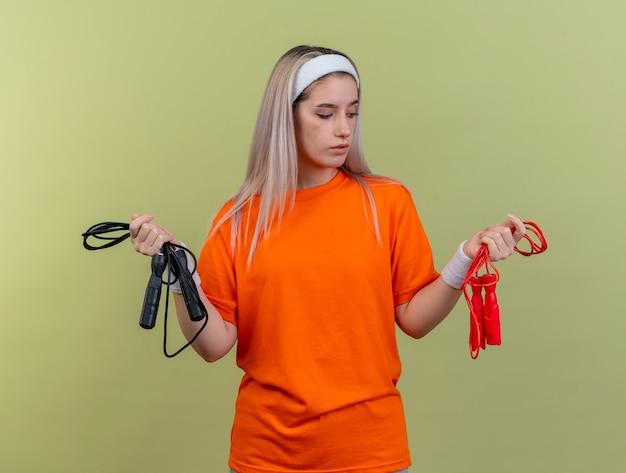Уверенная молодая кавказская спортивная девушка с подтяжками в головной повязке и браслетах держит и смотрит на скакалки