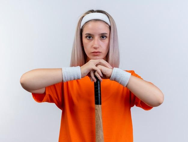 머리띠와 팔찌를 착용하는 중괄호와 자신감이 젊은 백인 스포티 한 소녀는 야구 방망이를 거꾸로 보유하고 있습니다.