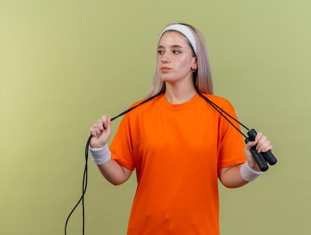 Уверенная молодая кавказская спортивная девушка с подтяжками, носящая повязку на голову и браслеты, держит скакалку вокруг шеи, глядя в сторону