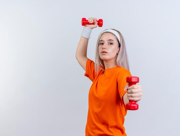 Уверенная молодая кавказская спортивная девушка с подтяжками, носящая повязку на голову и браслеты, стоит боком, держа гантели, изолированные на белой стене с копией пространства
