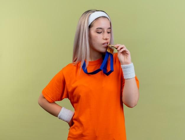 Fiduciosa giovane ragazza sportiva caucasica con bretelle che indossa fascia e braccialetti finge di mordere la medaglia d'oro