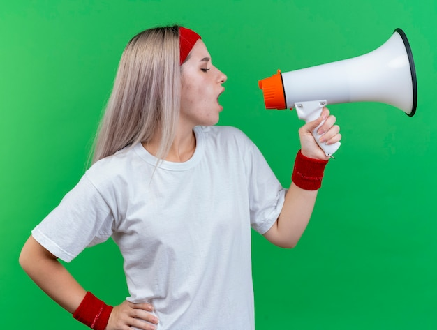 Fiduciosa giovane ragazza sportiva caucasica con bretelle che indossa fascia e braccialetti parla in un altoparlante guardando a lato