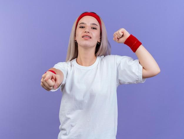 Fiduciosa giovane ragazza sportiva caucasica con le parentesi graffe che indossa la fascia